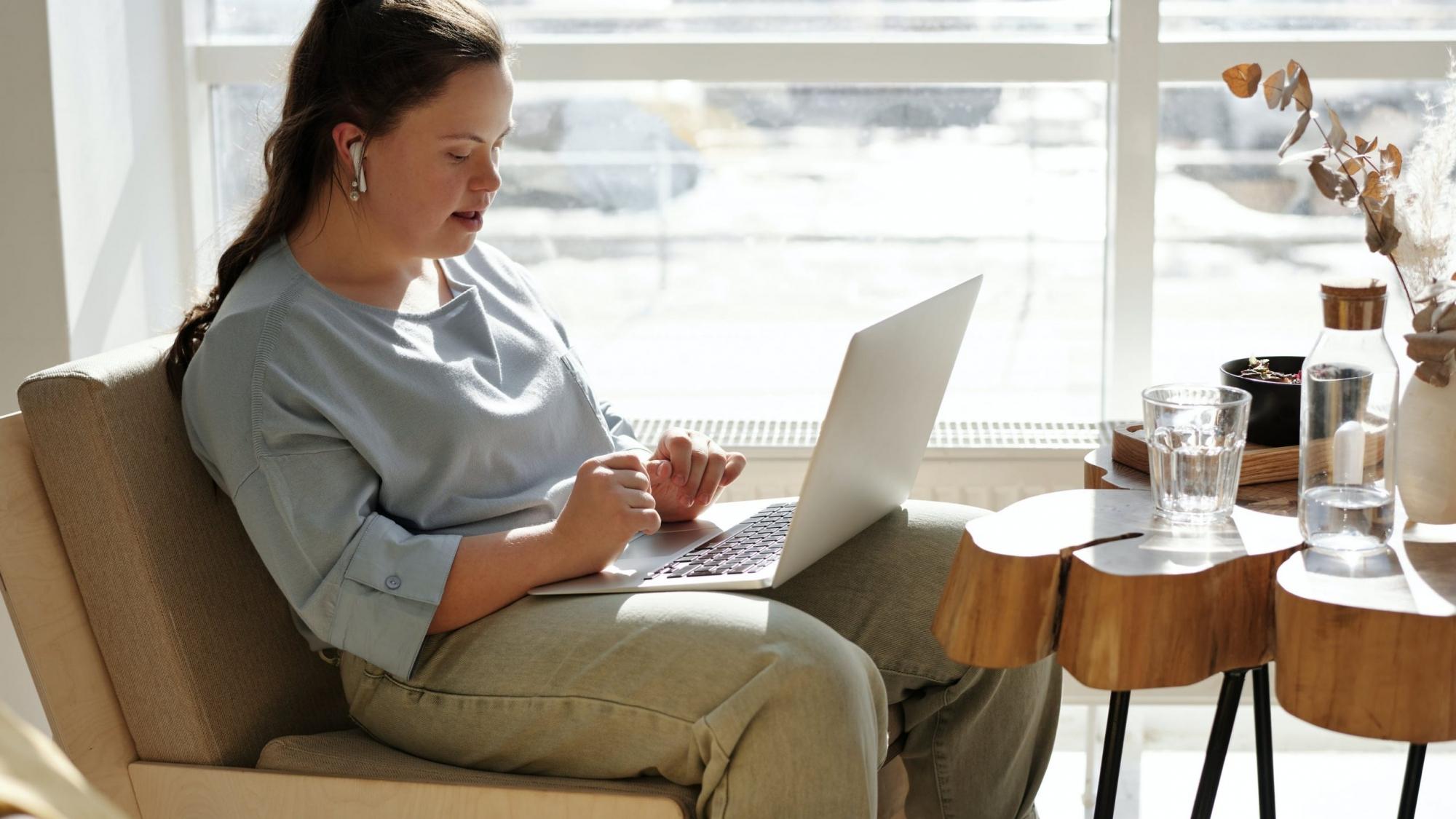 Mädchen mit Downsyndorm an Laptop